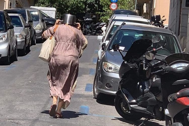 H Viral φωτογραφία της ημέρας: Η γυναίκα στο Κολωνάκι που τρέχει με την κατσαρόλα στο κεφάλι μετά τον σεισμό